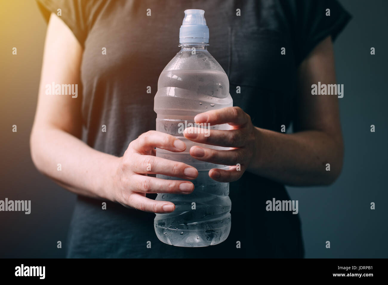 Woman with bottle of fresh drinking water for refreshment and rehydratation - Stock Image