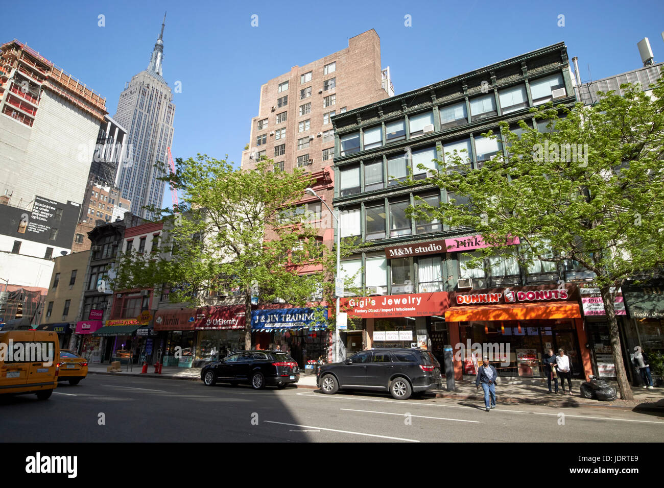 small shops on 6th avenue chelsea with view of the empire state building New York City USA - Stock Image