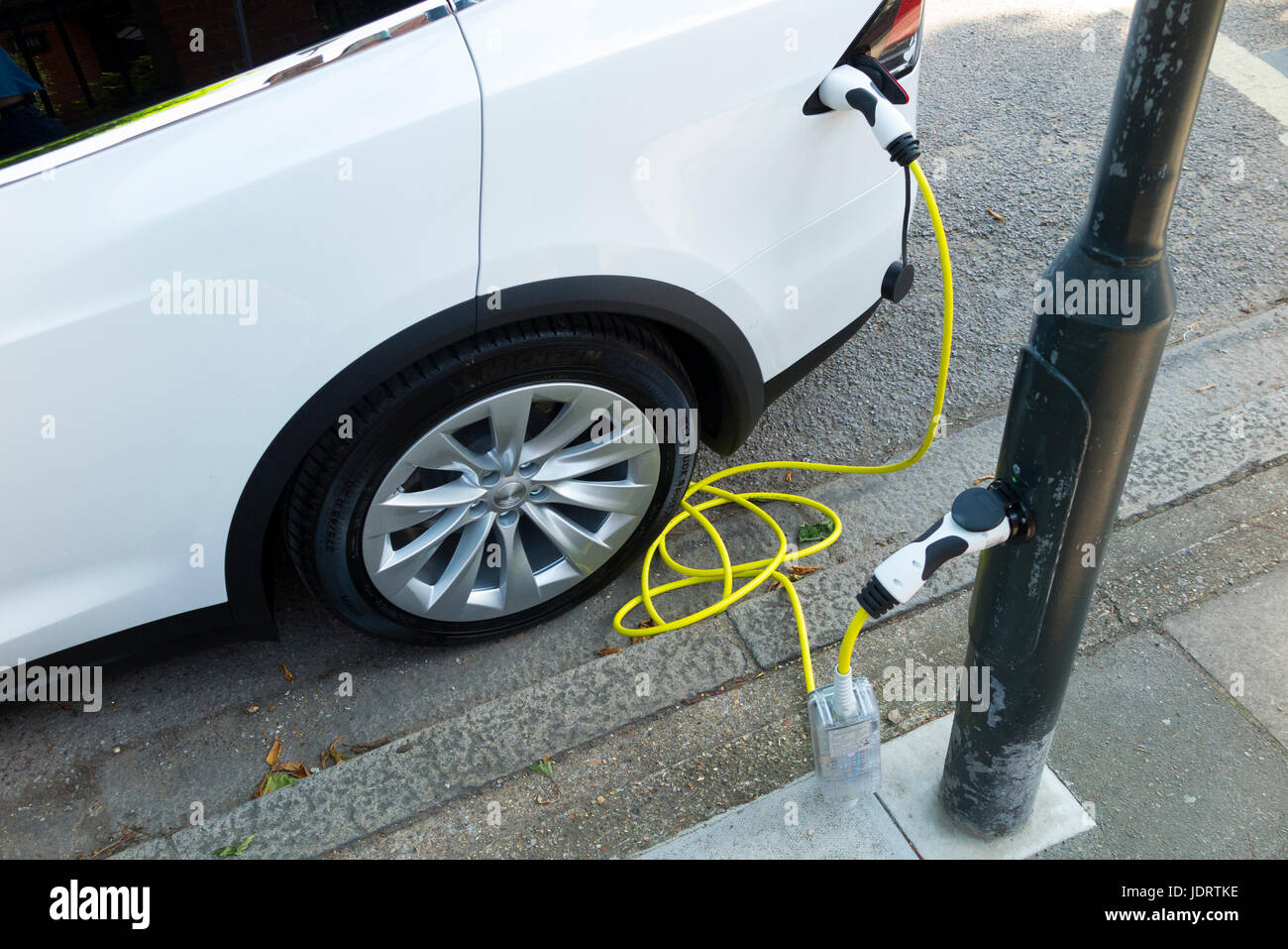 An electric car charger conversion by Ubitricity: smart cable on a street lamp which can now be used to charge a - Stock Image