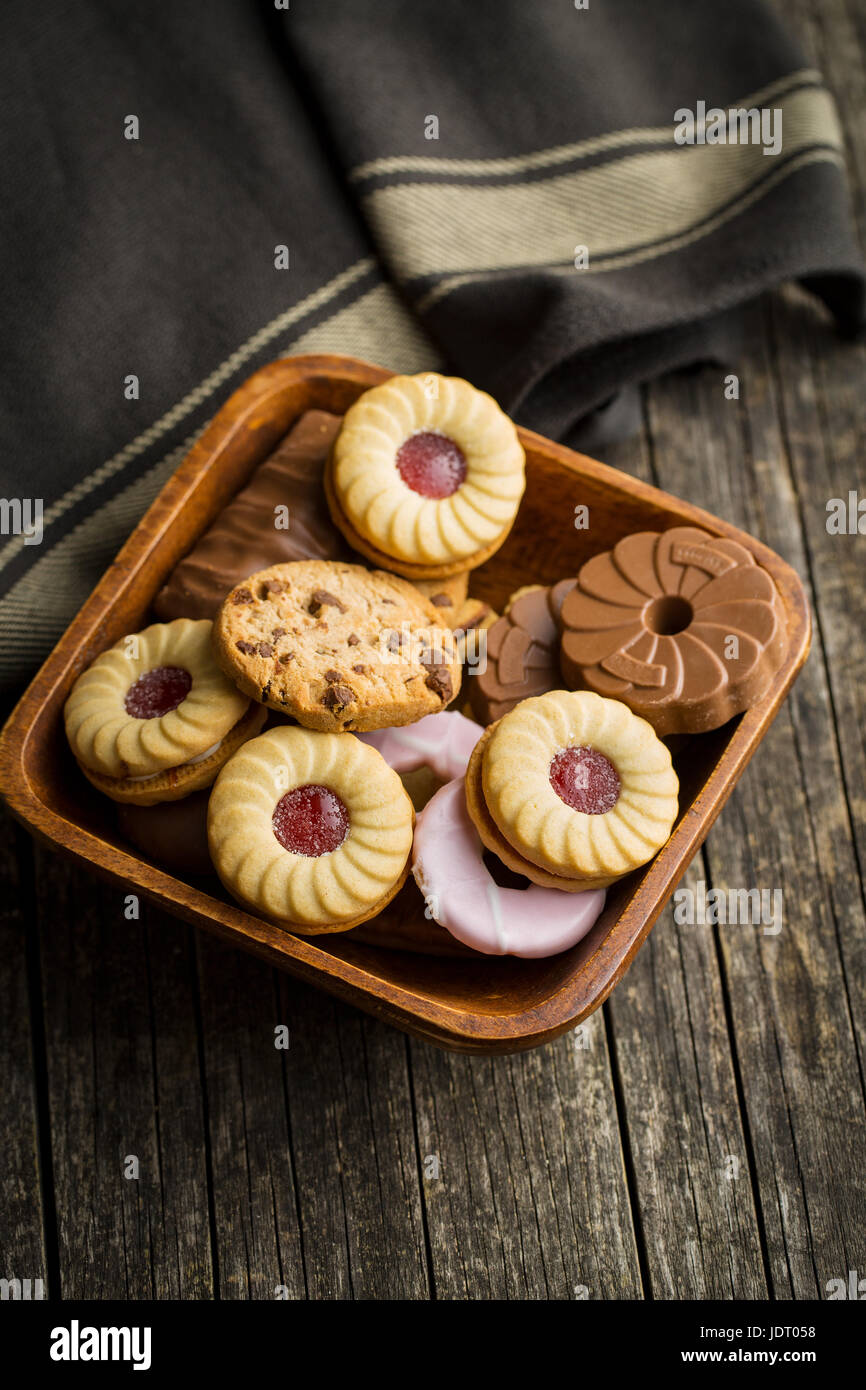 Various sweet biscuits on old wooden table. - Stock Image