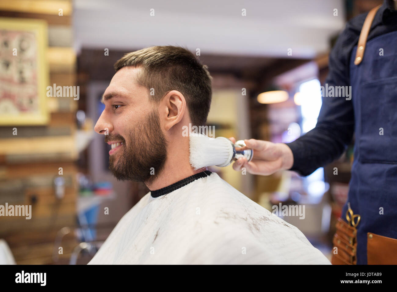 barber with brush cleaning male neck at barbershop - Stock Image