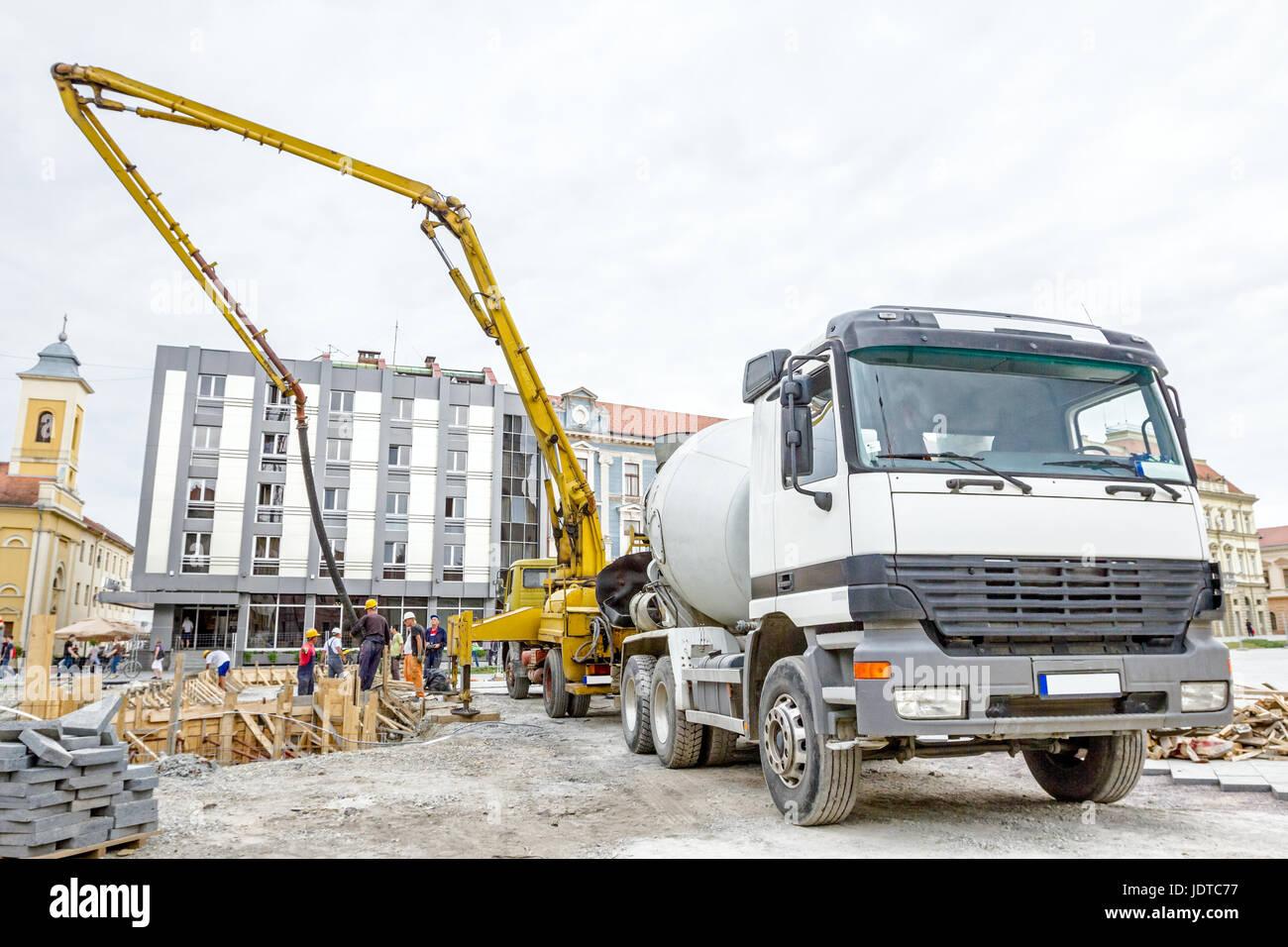 Truck mixer is pouring concrete into concrete pump for casting. - Stock Image