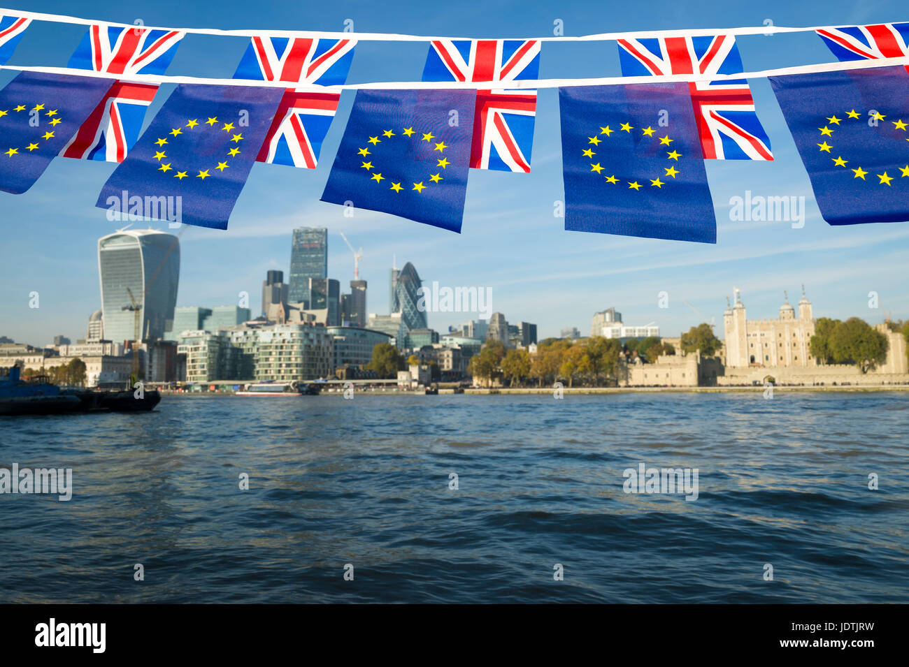 EU and UK bunting flags flying in front of the City of London, England skyline over the River Thames - Stock Image