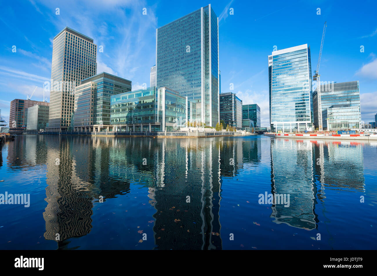 Shiny Canary Wharf skyscrapers towering above and reflecting in the docks of the River Thames in London. - Stock Image