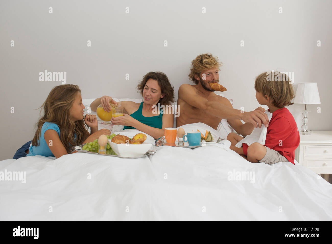 Young familiy having breakfast in bed - Stock Image