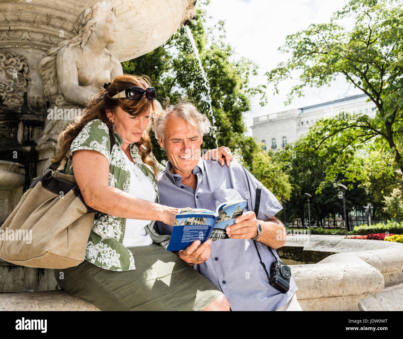 Older couple reading travel guide - Stock Image