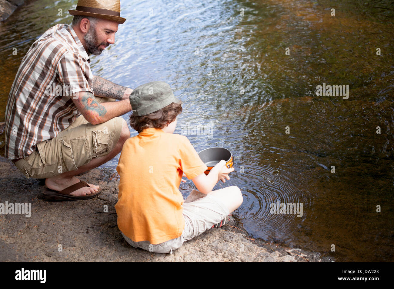 Father and son panning for gold in river - Stock Image