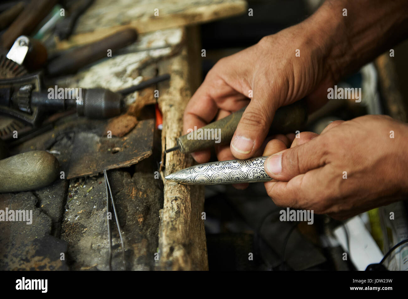 Close up of artisan carving metal - Stock Image