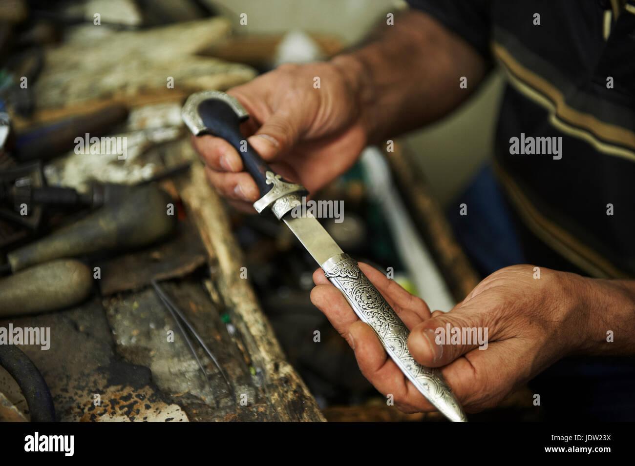 Artisan holding carving metal - Stock Image