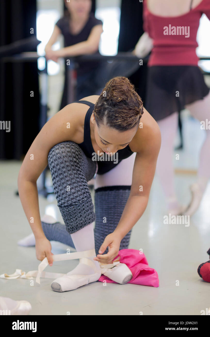 Ballet dancer tying on pointe shoes - Stock Image