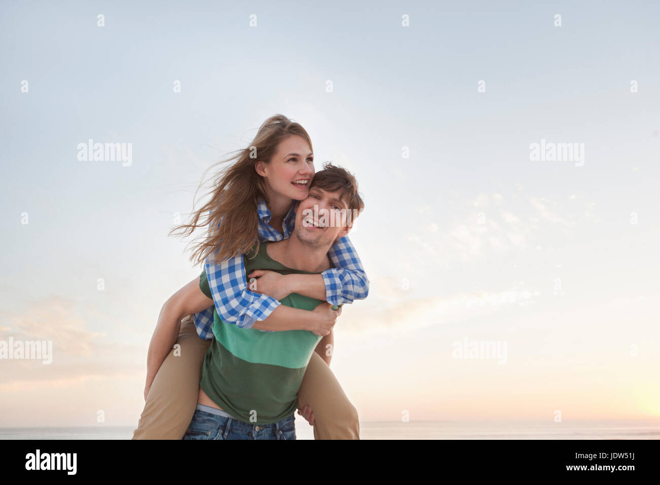 Couple on beach, man giving woman piggy back - Stock Image