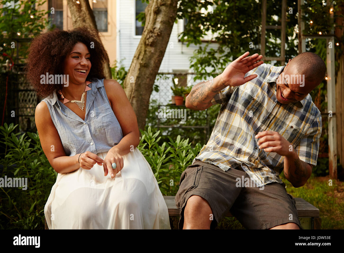 Mid adult man laughing with woman at garden party Stock Photo