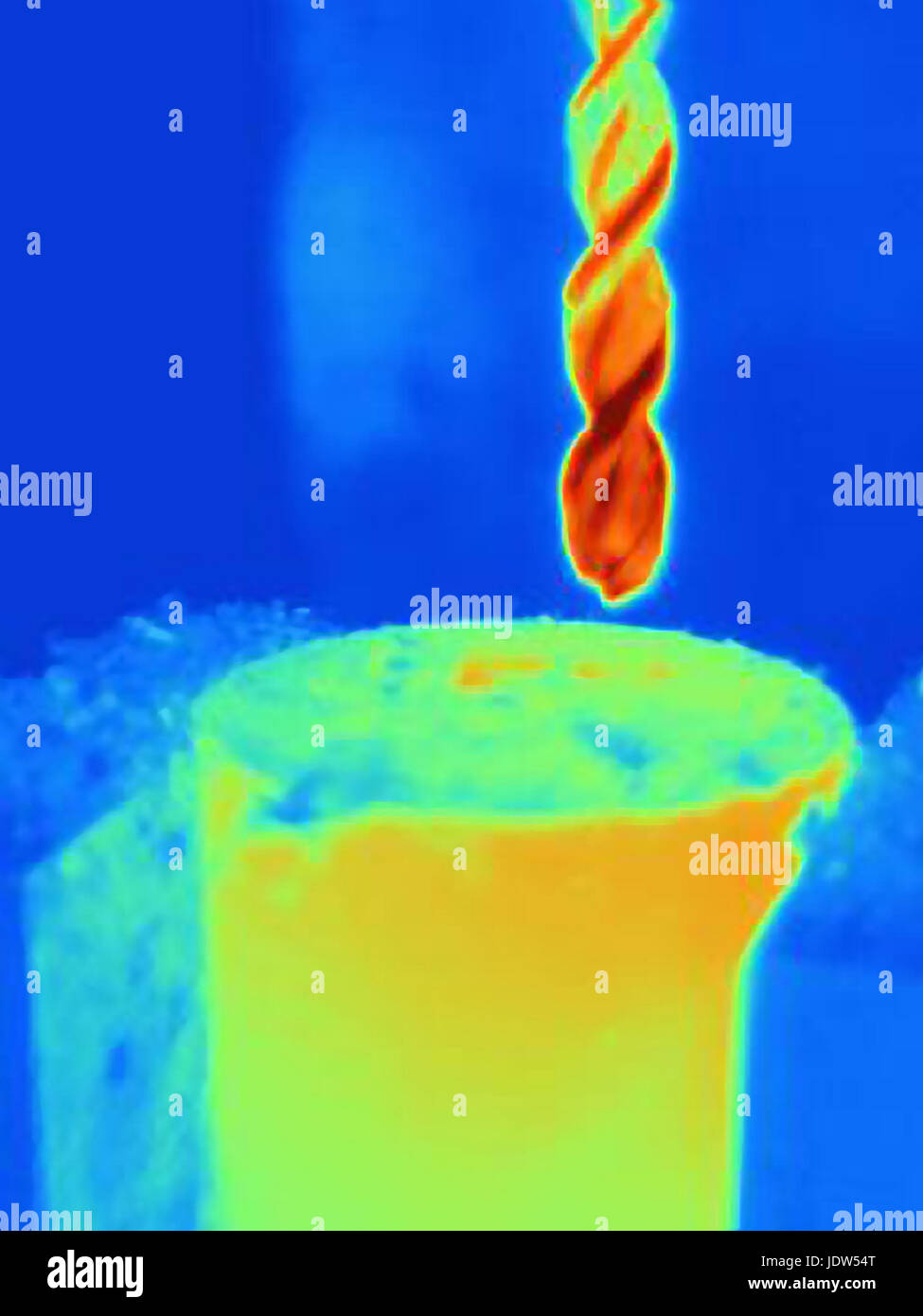 Thermal image of drilling into a component, showing the heat buildup on the drill bit and the part - Stock Image