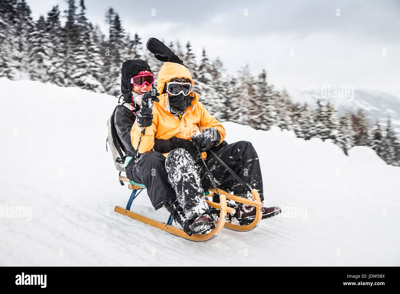 Young couple sledging, Bramberg am Wildkogel, Austria - Stock Image