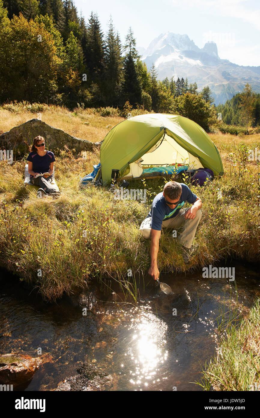 Couple camping by stream, Chamonix, Haute Savoie, France - Stock Image