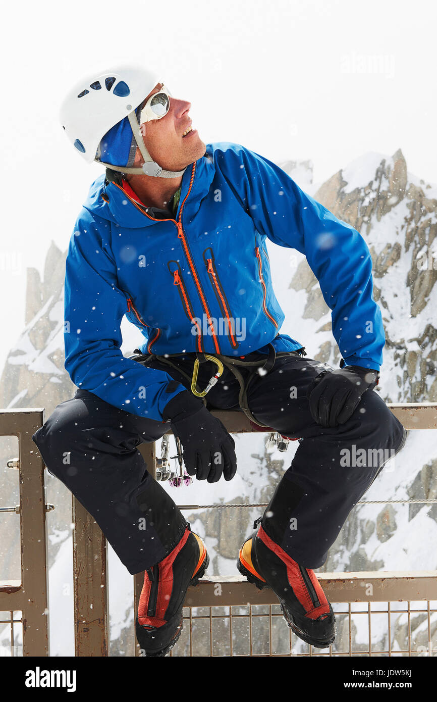 Portrait of man wearing climbing helmet looking up - Stock Image