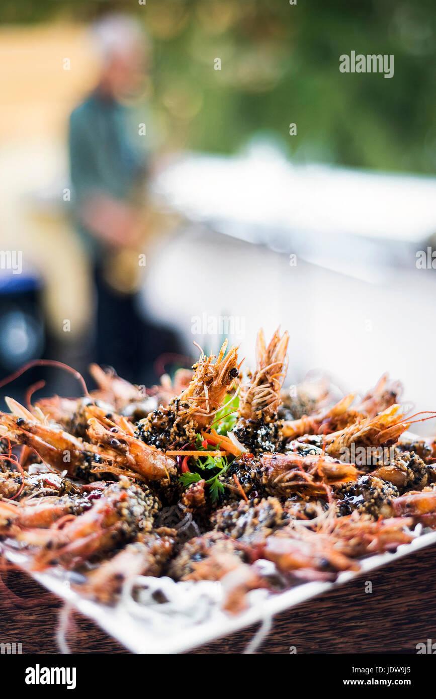 gourmet cambodian kampot pepper sauce prawns in modern outdoor bar - Stock Image
