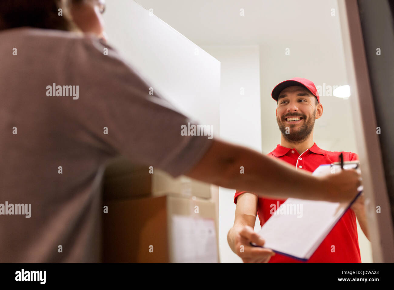 deliveryman and customer with parcel boxes at home - Stock Image