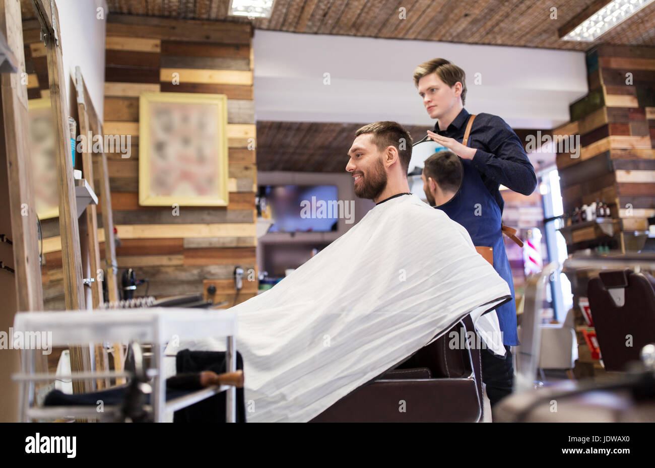 man and hairdresser with mirror at barbershop - Stock Image
