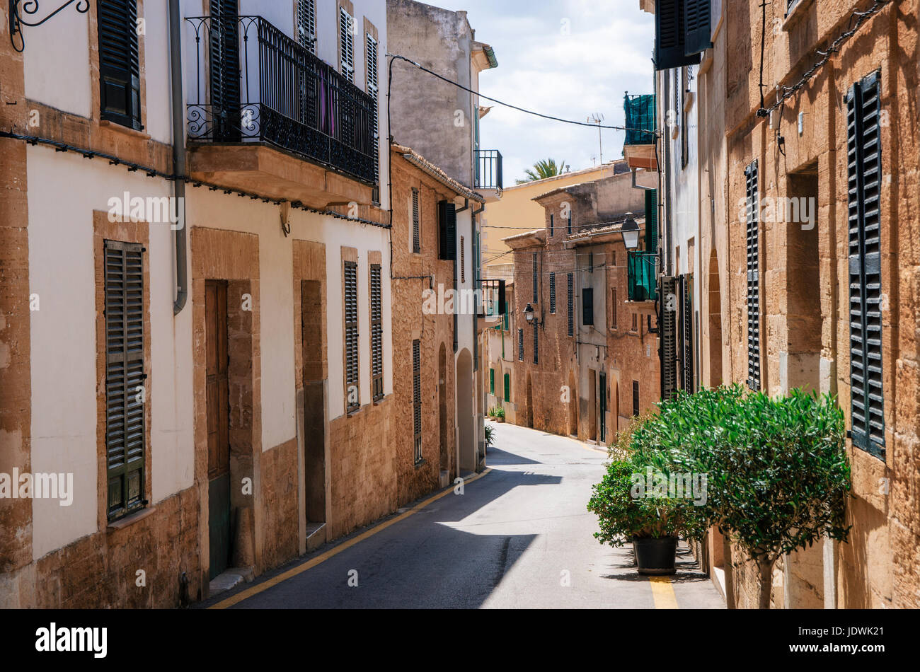 Alcudia, Mallorca, Spain - May 23, 2015: Narrow street of historical town part of Alcudia with its traditional house - Stock Image