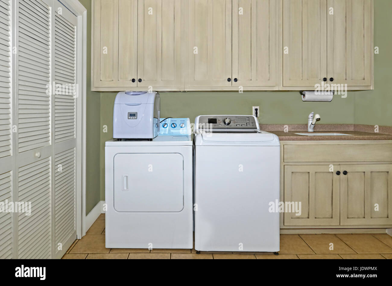 A laundry room with washer,dryer,ice maker,sink,cabinets,and a pantry area.  The cabinets have a light antiqued - Stock Image