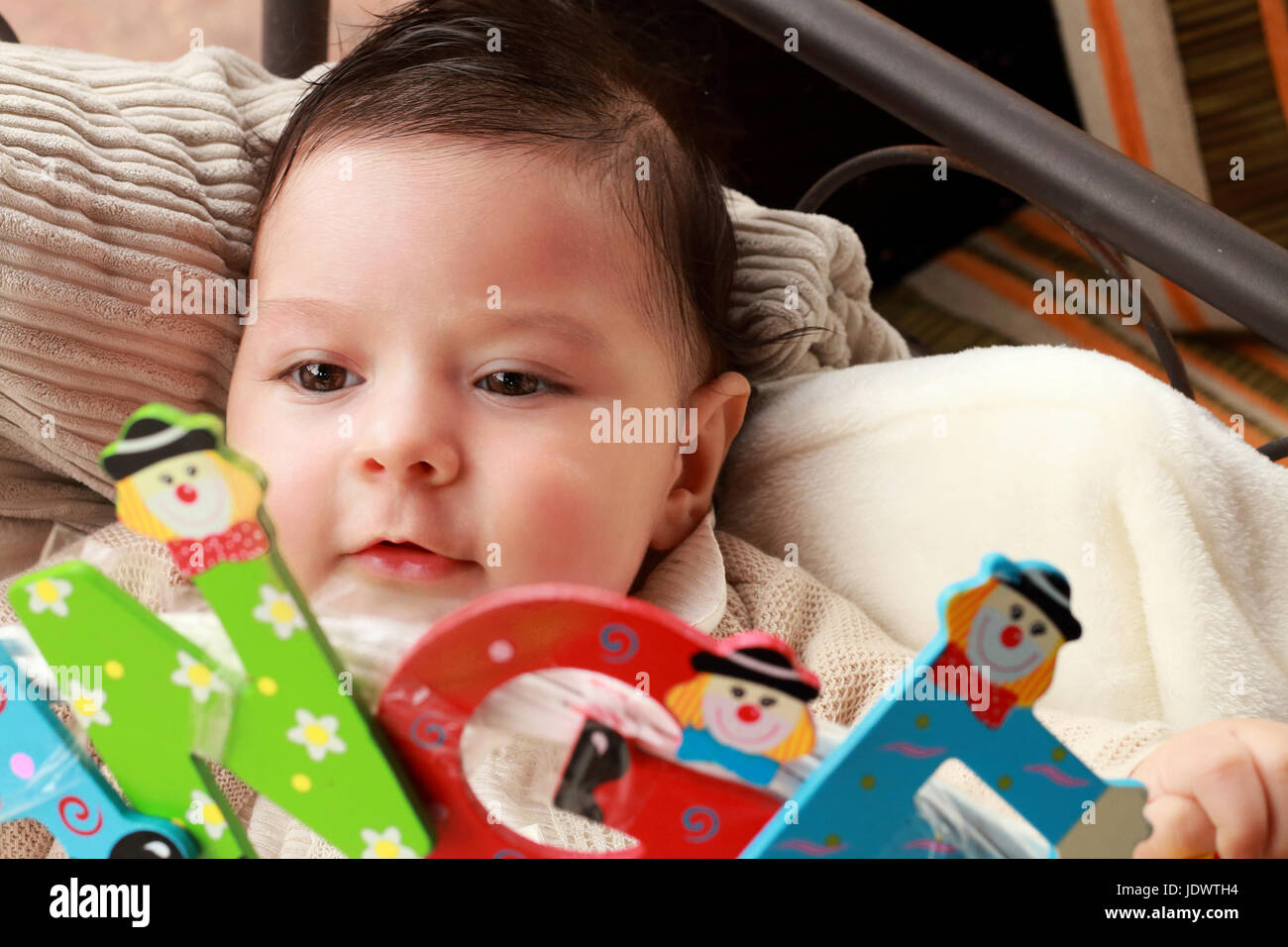 Baby playing with colorful letters - Stock Image
