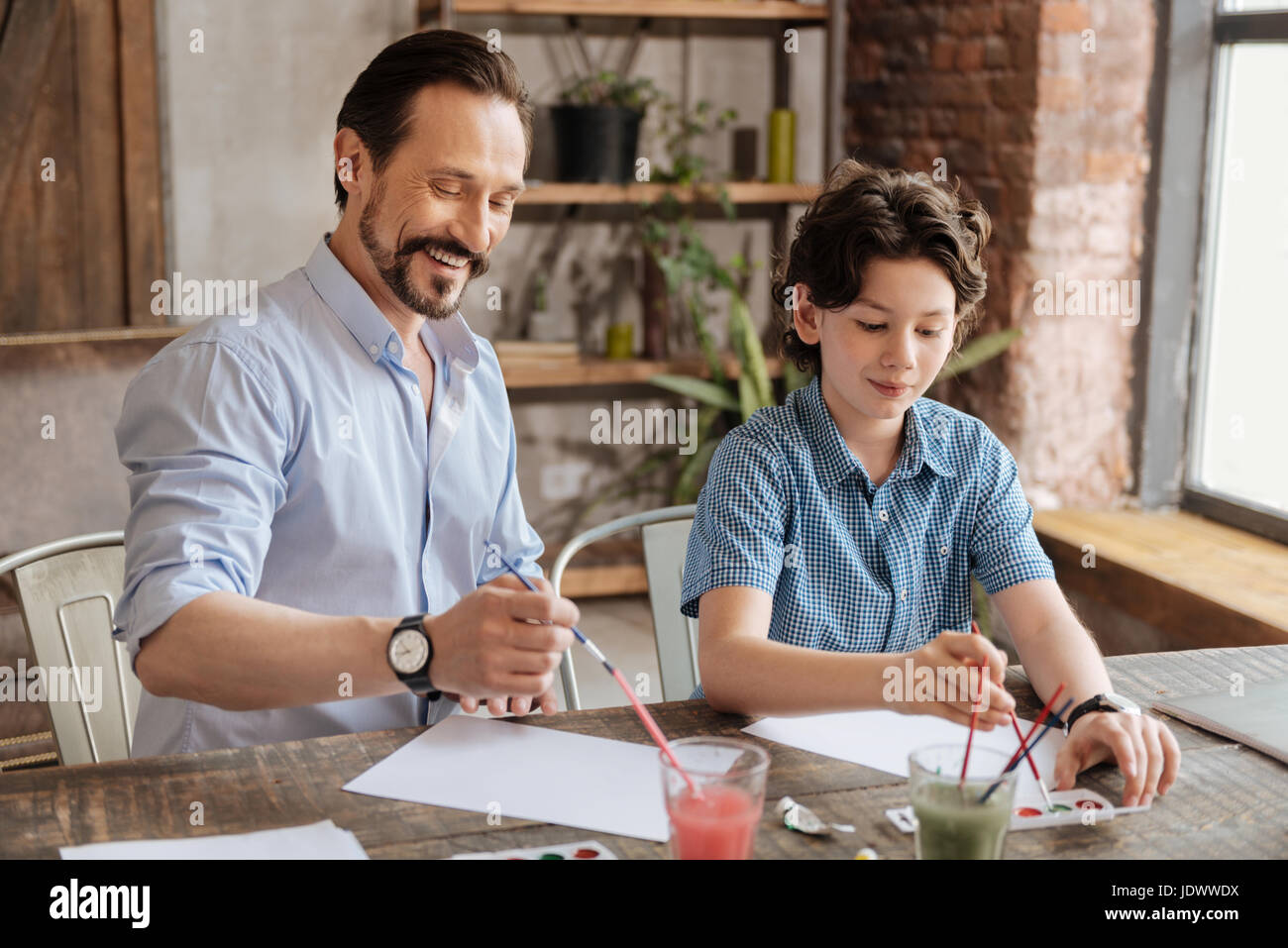 Happy father and his son focused on painting - Stock Image