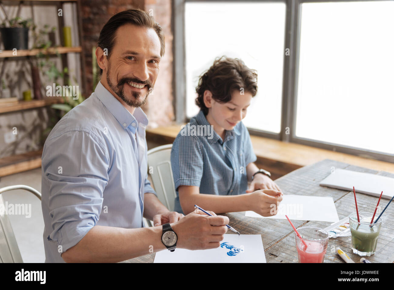 Young father being happy to paint with his son - Stock Image