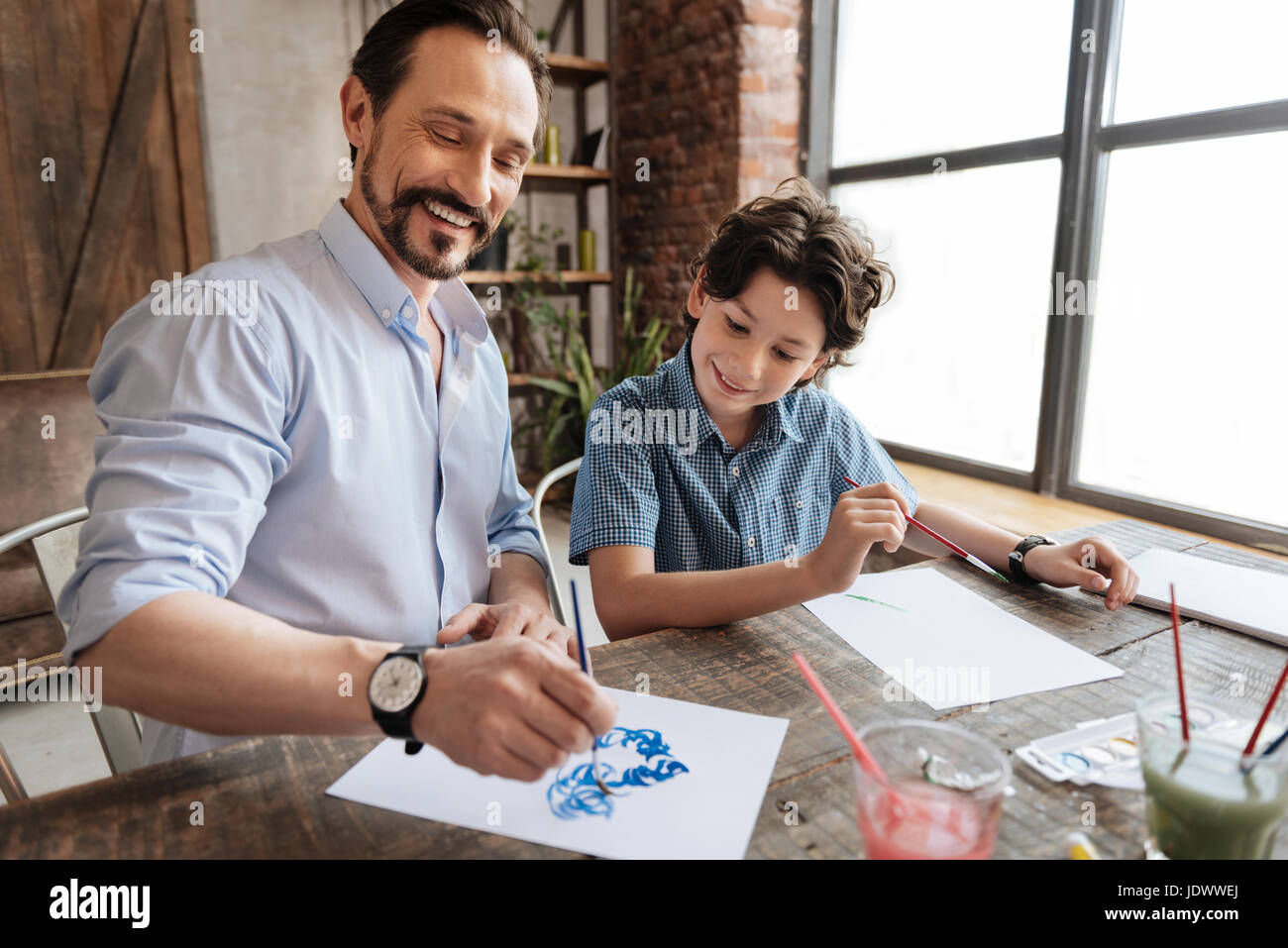 Sweet teenager copying the picture of his father - Stock Image