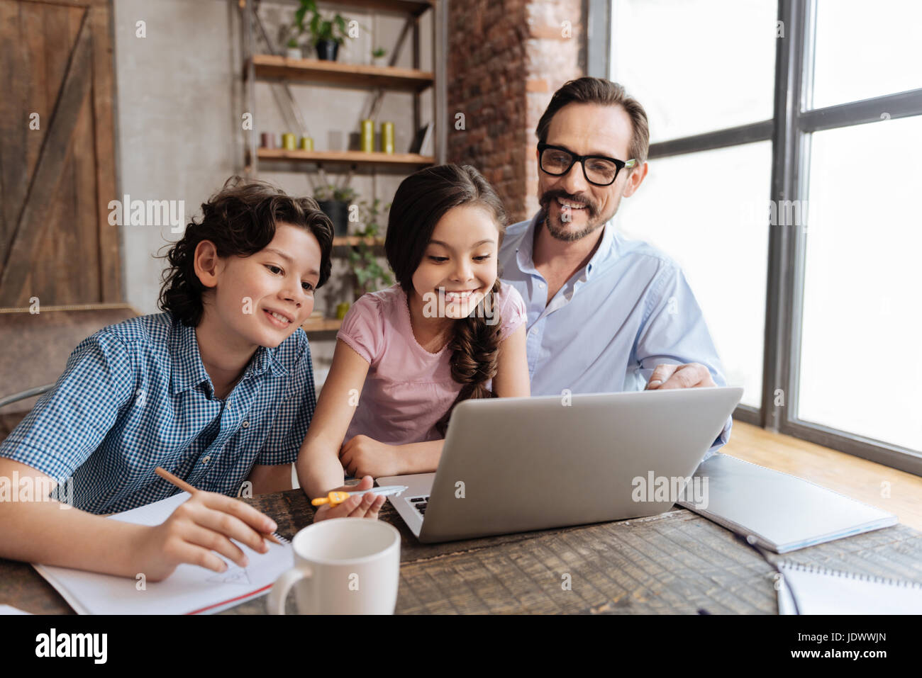 Upbeat family watching an educational video - Stock Image