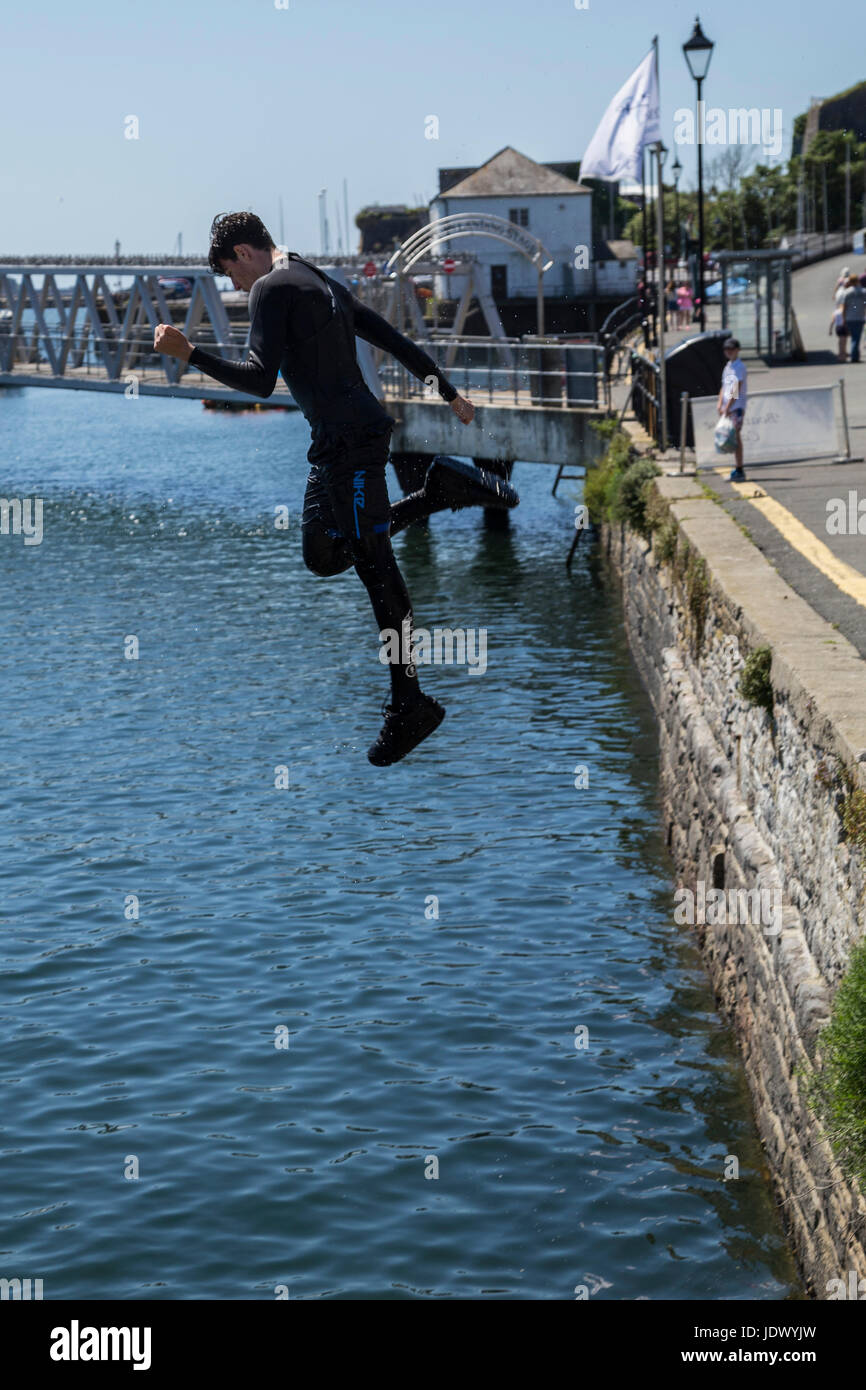 A boy jumps into the water at Barbican Wharves, Plymouth Harbour. - Stock Image