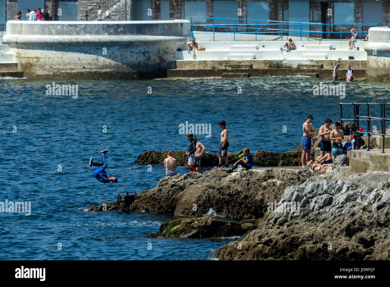 Youths dive and jump into the sea at Plymouth Harbour, Devon, UK - Stock Image