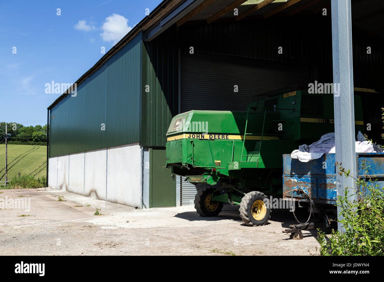 John Deere combine in farm yard,agriculture, combine, crop, deere, farm, green, harvester, john, morning, rural, Stock Photo