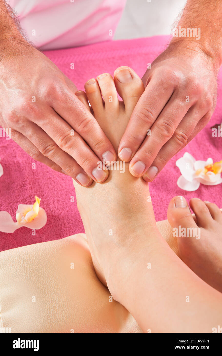 Closeup of male therapist giving foot massage to female customer at beauty spa Stock Photo