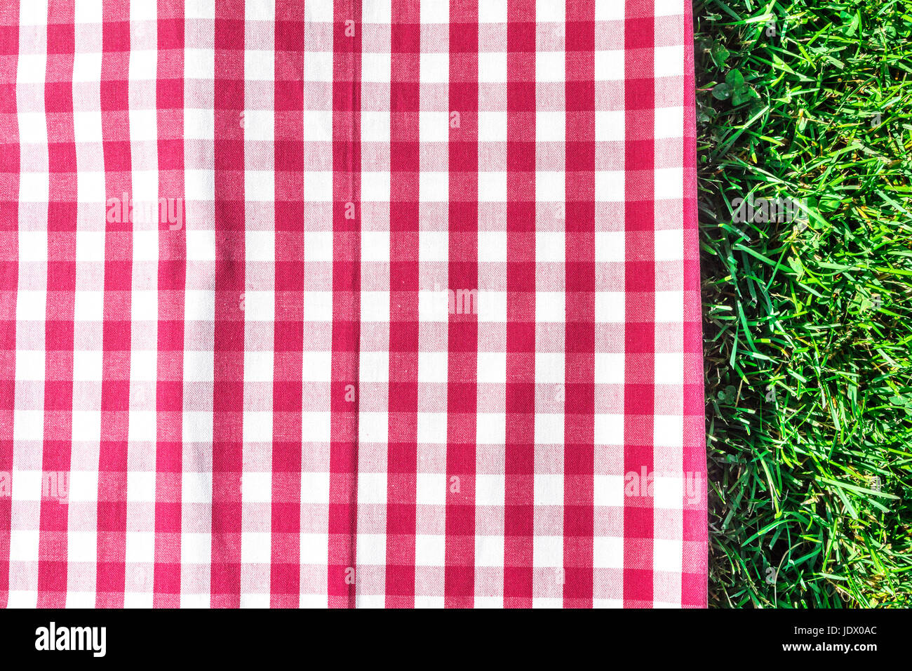 Red gingham tablecloth on green grass with copyspace - Stock Image