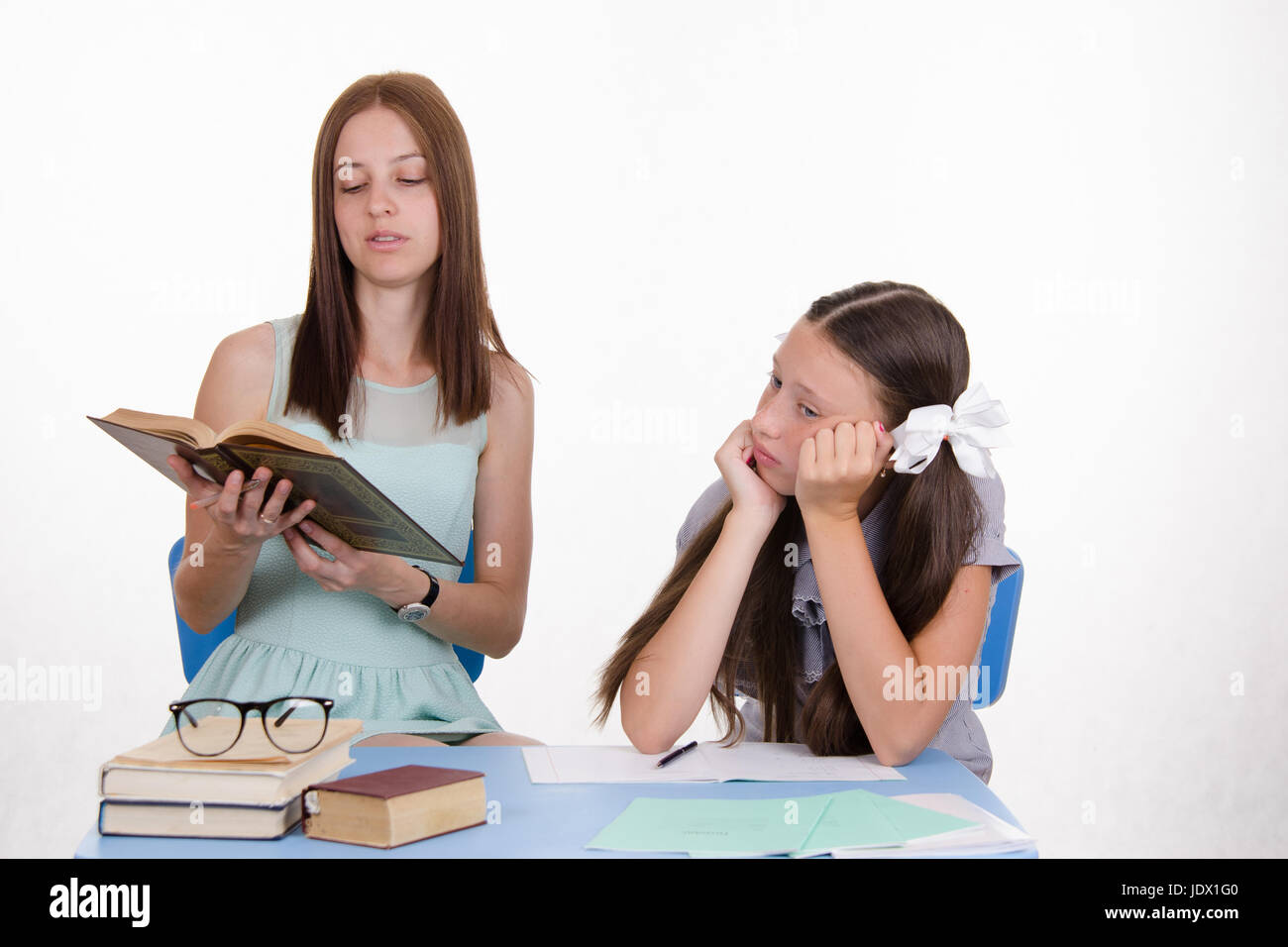 Teacher teaches the student sitting with him at the table - Stock Image