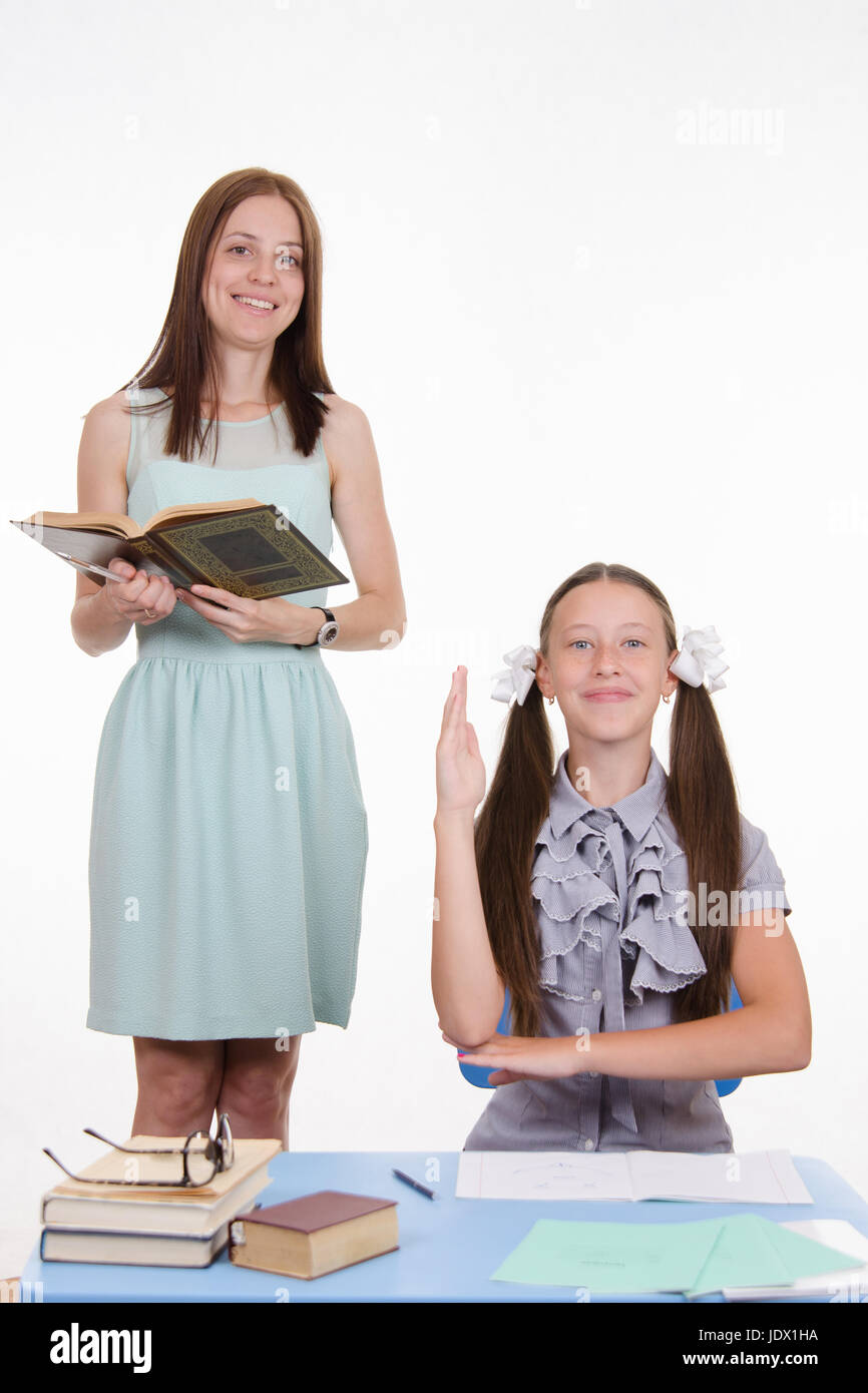 Teacher standing at desk behind which sits a diligent student - Stock Image