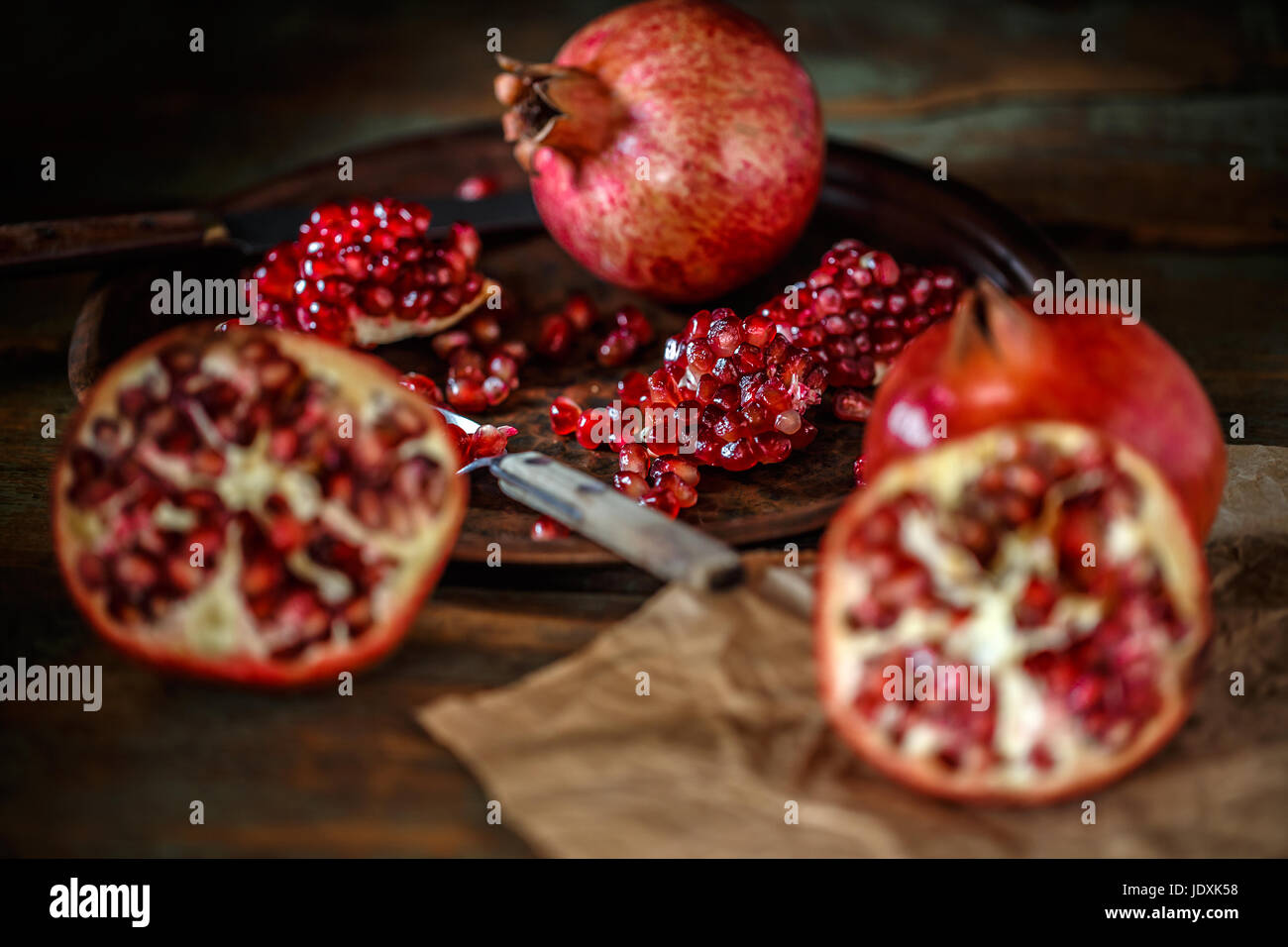 Fresh juicy pomegranate, whole and cut  on vintage background - Stock Image