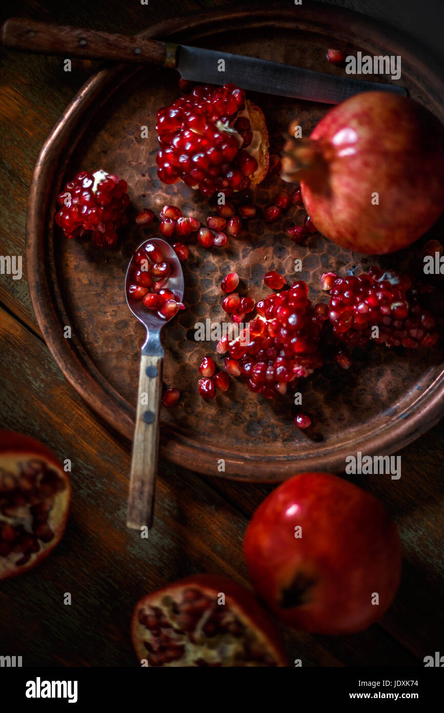 Healthy food concept, juicy pomegranates on vintage background - Stock Image