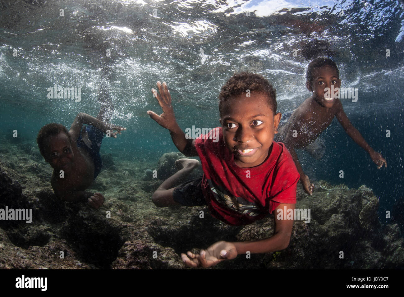 Kids splashing in Ocean, Melanesia, Pacific Ocean, Solomon Islands - Stock Image