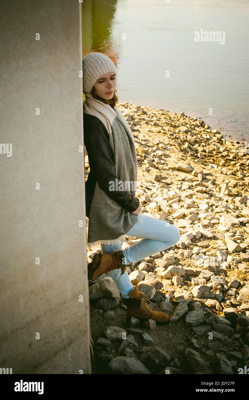 young woman wearing a scarf and jacket, standing on the river bank with his back to the support of the bridge bent - Stock Image