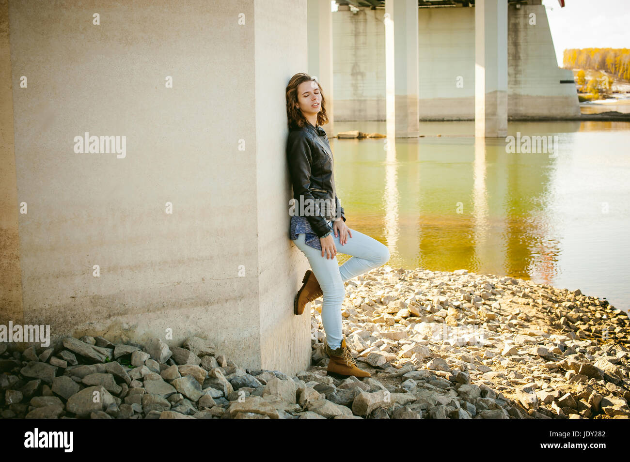 young woman in blue jeans and jacket, standing on the river bank with his back to the support of the bridge bent - Stock Image