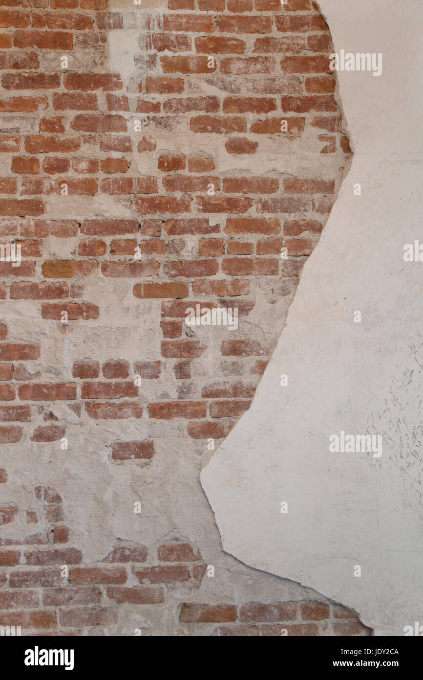 Abstract red bricks and plaster background damaged gritty texture. - Stock Image