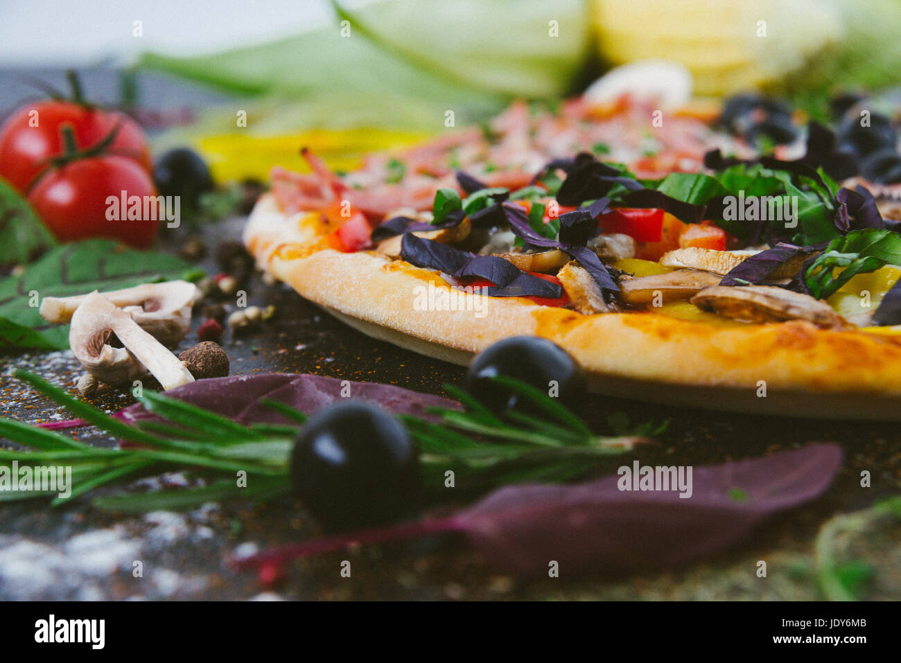 Italian pizza with mozzarella, black olives, prosciutto and tomatoes - Stock Image