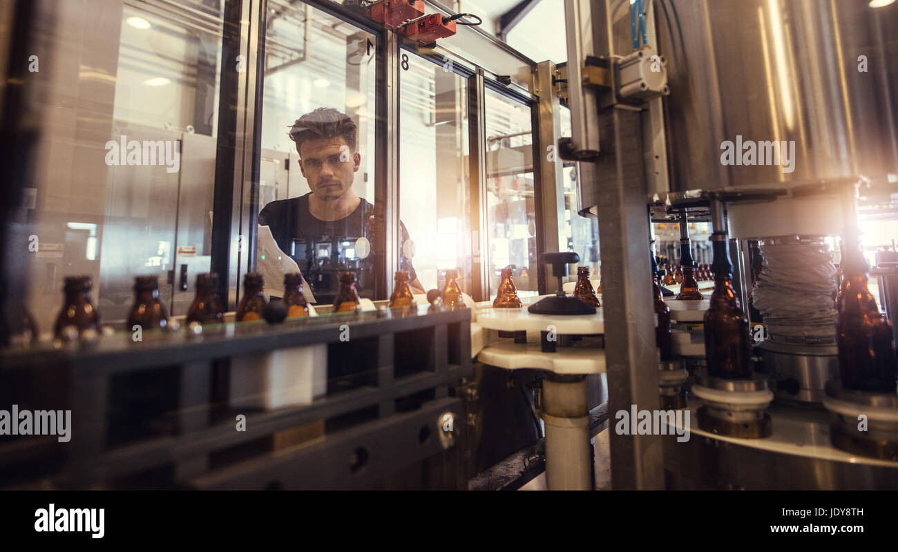 Factory worker looking at conveyor with beer beverage bottles moving. Brewer supervising the process of beer bottling - Stock Image