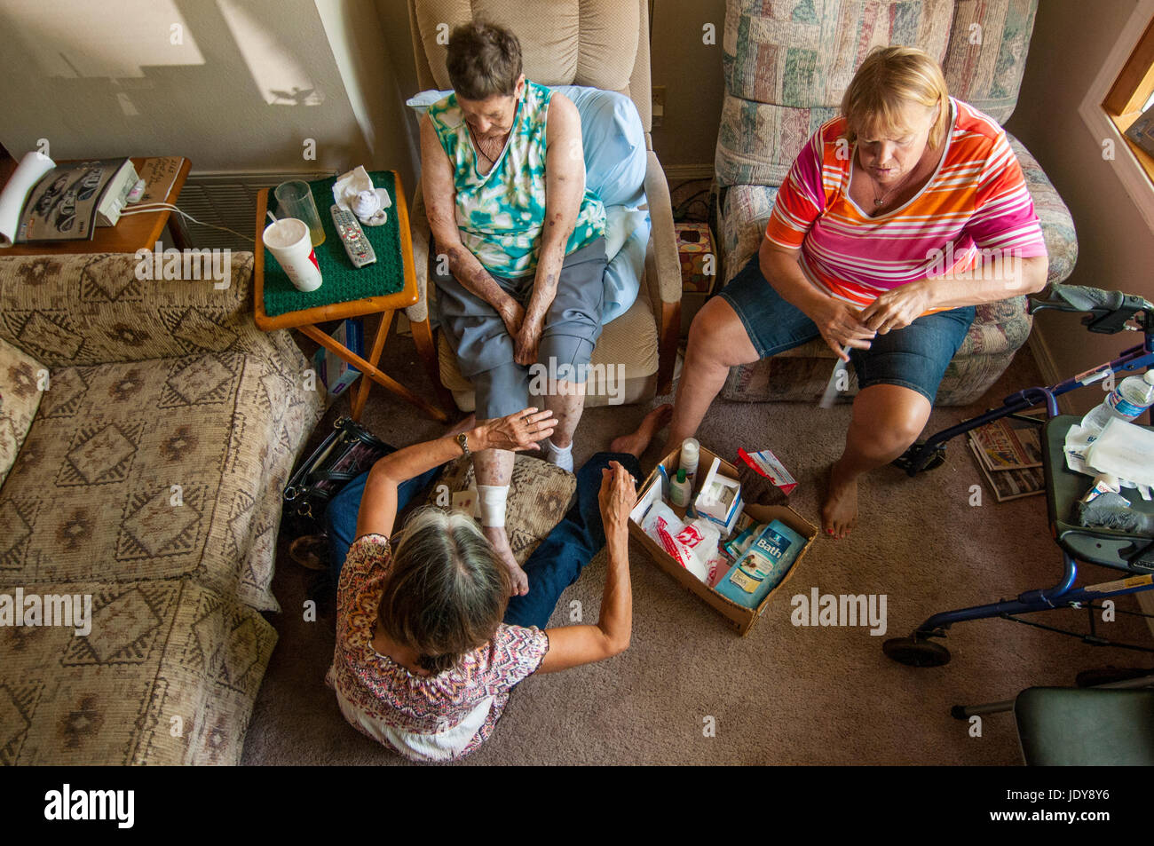 Two 50 55 Year Old Caucasian Sisters Help Their 84 Mother With Bandages Photographed From Above