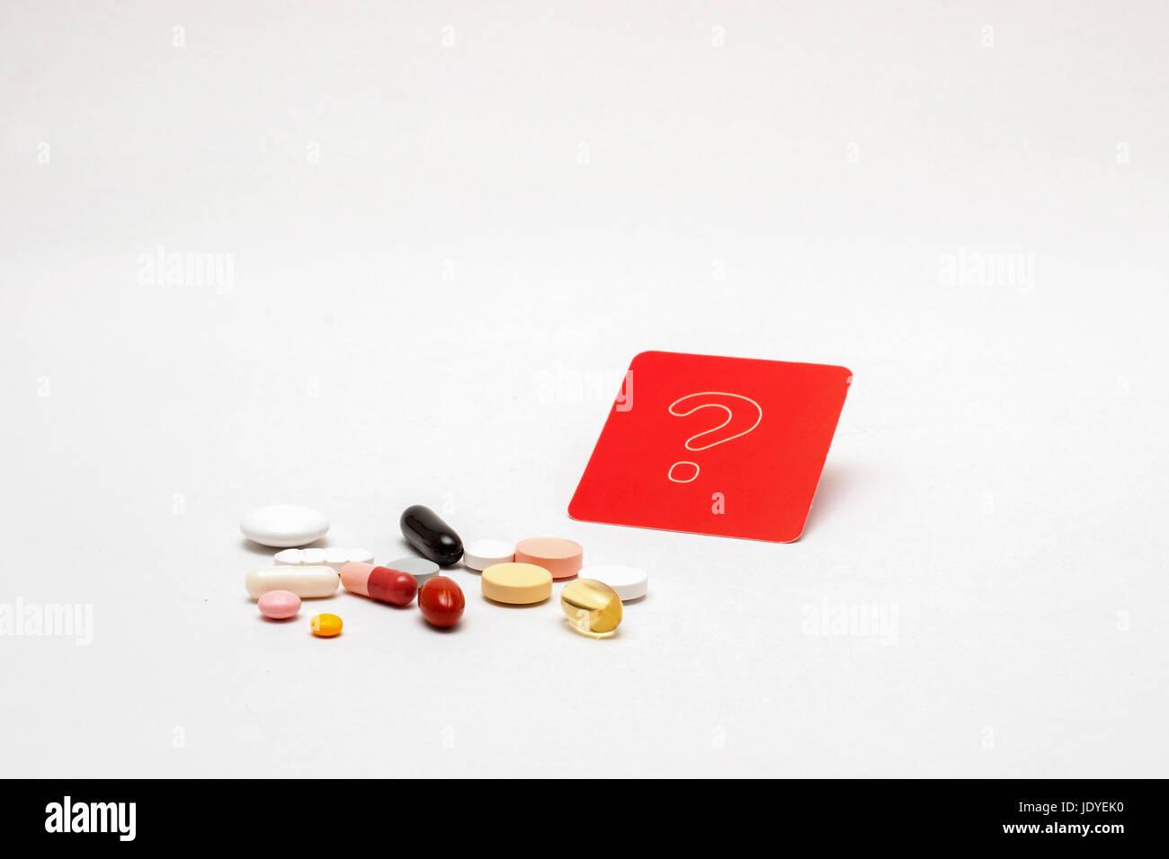 verschiedene bunte Tabletten mit rotem Fragezeichen-Schild, isoliert Stock Photo