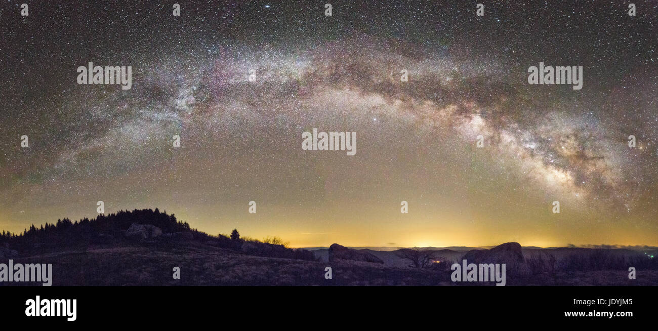 The full arch of the Milky Way stretches across the horizon on a clear night from atop the highest point in West - Stock Image