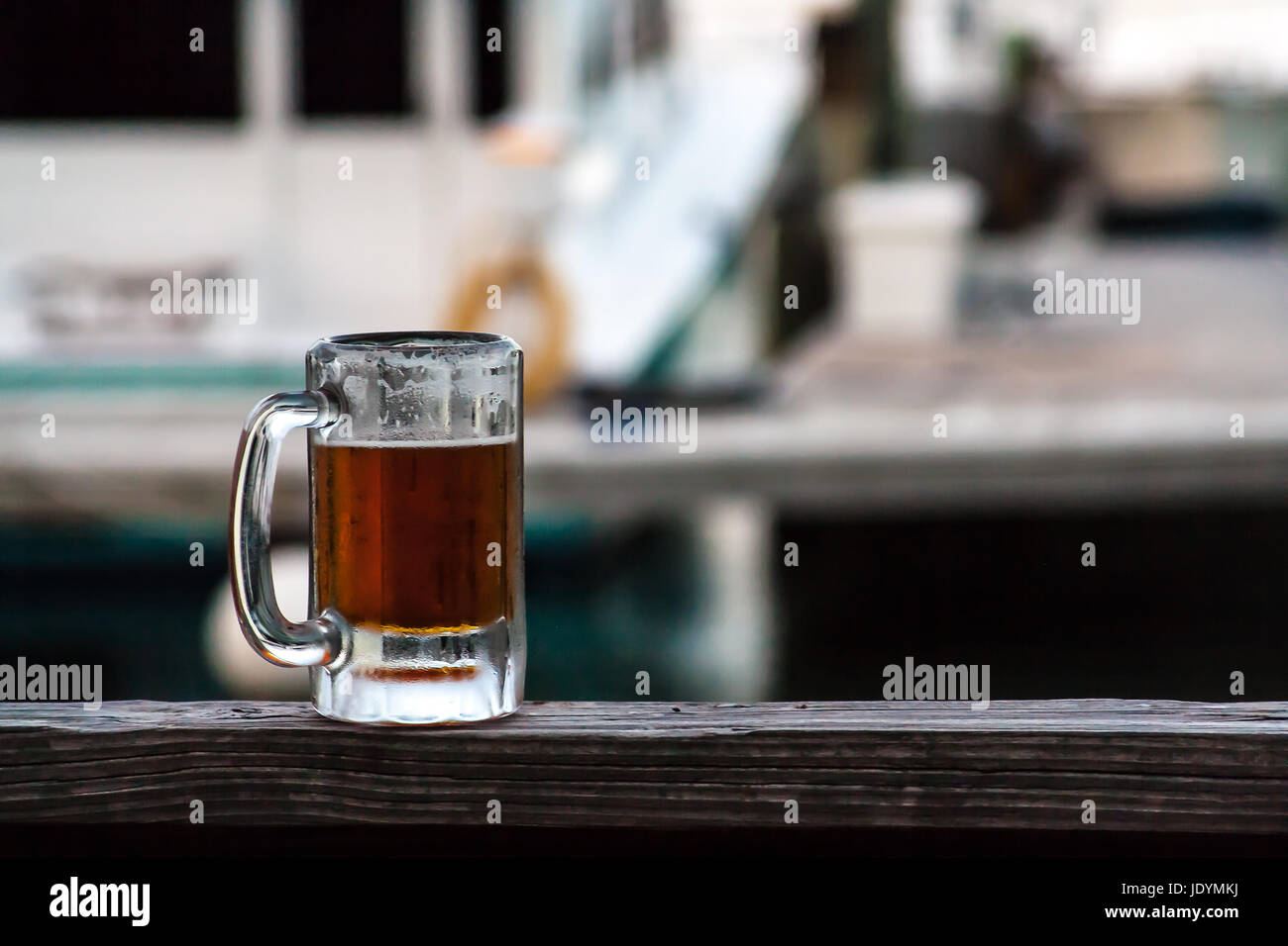 Close up of a beer during happy hour with boats in the background - Stock Image