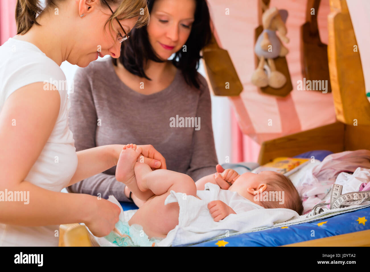 Midwife examining newborn baby at postnatal care in practice - Stock Image